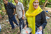 26 OCTOBER 2012 - PULASAIZ, NARATHIWAT, THAILAND:  A woman holds the water mixture that will be used to bless a young bull before sacrificing it for Eid al-Adha in the villiage Pulasaiz, in the province of Narathiwat, Thailand. The sacrificed cow is butchered and divided into seven portions. The meat is shared with families of lesser means, widows and orphans. It is the one day of the year that some people in the community get to eat beef (In Muslim communities in Thailand, cows are usually sacrificed. In other Muslim countries it is often sheep.) Eid al-Adha, also called Feast of the Sacrifice, is an important religious holiday celebrated by Muslims worldwide to honor the willingness of the prophet Ibrahim (Abraham) to sacrifice his firstborn son Ishmael as an act of submission to God, and his son's acceptance of the sacrifice before God intervened to provide Abraham with a ram to sacrifice instead. In 2012 Eid al-Adha was celebrated Oct 25 - 26.    PHOTO BY JACK KURTZ