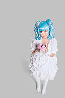 Full length portrait of cute woman in doll costume holding toy basket over gray background