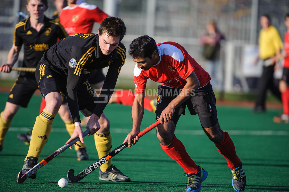 Yasser Khan of Holcombe takes on Richard Lawrence of Beeston during their match in the England Hockey Men's Cup
