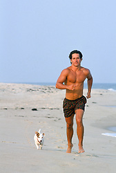 hot man running on the beach with his Jack Russell Puppy