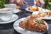 Breakfast with croissant, pastry and coffee at outdoor cafe.