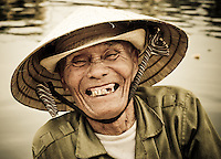 An elderly boatman flashes a friendly smile while waiting for tourists in Hoi An, Vietnam, Southeast Asia in April, 2008.