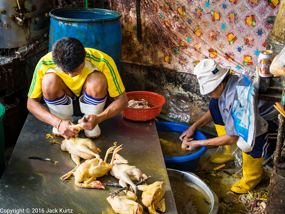 """12 JANUARY 2016 - BANGKOK, THAILAND: Workers slaughter chickens in the live poultry section of Khlong Toey Market (also spelled Khlong Toei) in Bangkok. On Monday the Thai Ministry of Public Health instructed government agencies to watch for any signs of """"bird flu"""" during the winter season, and warned the public to avoid contact with any birds that appear sickly. The latest data from the World Health Organization showed the continuous transmission of avian flu in various countries, both in people and birds. Bird Flu is endemic in China, Vietnam and Indonesia, all important Thai trading partners. There have been no recorded outbreaks of Bird Flu in humans in Thailand several years.      PHOTO BY JACK KURTZ"""