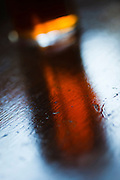 Reflection of English ale on wooden bar, London, UK