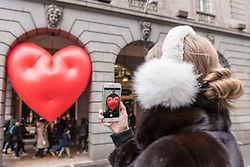 "© Licensed to London News Pictures. 14/02/2018. LONDON, UK. A tourist takes a photo of a giant chubby heart balloon at The Ritz Hotel in Piccadilly as part of ""Chubby Hearts Over London"",  a design project conceived by Anya Hindmarch.  Supported by the Mayor of London, the British Fashion Council and the City of Westminster giant chubby heart balloons will be suspended over (and sometimes squashed within) London landmarks as a declaration of love to the city starting on Valentine's Day and continuing throughout London Fashion Week.  Photo credit: Stephen Chung/LNP"