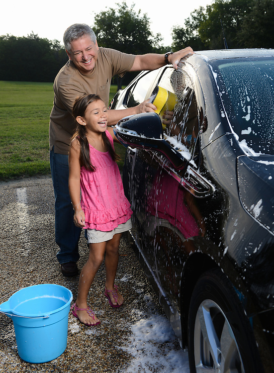 Father daughter wash car on a lifestyle photo shoot in Rockwall, Texas.