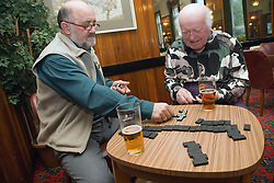 Two older men playing dominoes in the pub,