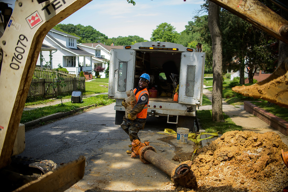 Photo by Matt Roth<br /> <br /> Baltimore City Department of Public Works supervisor Nathaniel Copeland carries a bag of concrete to the cavity while working with his crew to replace a fire hydrant at the intersection of Tyndale Ave., and Canfield Ave. in Baltimore, Maryland on Wednesday, May 29, 2013.