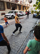 Mehmet plays soccer on his street.