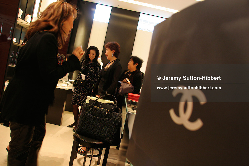 "GUESTS OF CHANEL IN NEW TOKYO STORE shopping for Chanel goods inside the new 'Chanel' store in Ginza, Tokyo, prior to the Chanel 'Coco å Tokyo' fashion show. The ""Coco a Tokyo' show was the first time clothes by Chanel, designed by Karl Lagerfeld, had been premiered outwith Paris, France."