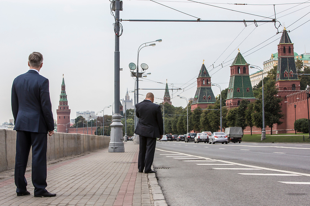 An aide, left, and a security guard await the arrival of Moscow Mayor Sergei S. Sobyanin and Kirill I, patriarch of the Russian Orthodox Church, before a meeting for Sobyanin's re-election campaign on a sidewalk between the Kremlin walls and the Moscow River on Thursday, August 29, 2013 in Moscow, Russia.