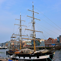 Tall Ship and Harp Bridge in Dublin, Ireland <br /> The Jeanie Johnston was a three-masted sailing vessel launched in 1848. The barque ship initially transported Irish immigrants to America during the Great Famine and returned with cargo such as wood. It sunk in 1855. This recreation was launched in 2000. When docked along the quay, the tall ship serves as a history museum and event center.  Behind it is the Samuel Beckett Bridge, one of River Liffey's newest landmarks.  It was cleverly designed by Santiago Calatrava to resemble a harp, Ireland's national symbol.  The 394 foot steel bridged opened for traffic in 2009. The waterfront buildings in the background are on Sir John Rogerson's Quay.