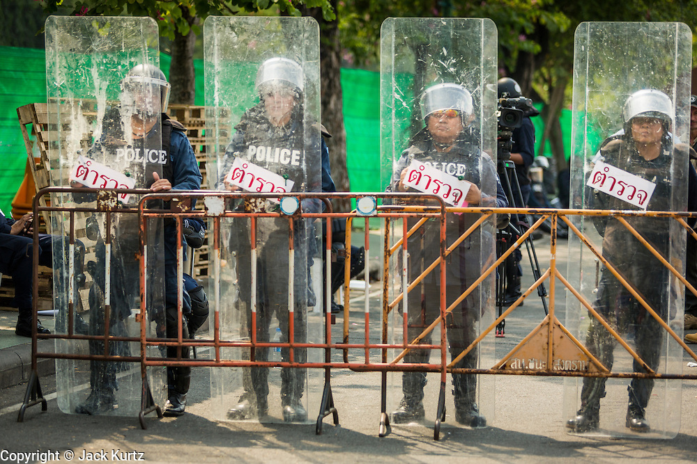 "09 DECEMBER 2013 - BANGKOK, THAILAND:  Thai riot police on duty in front of Government House in Bangkok. Thai Prime Minister Yingluck Shinawatra announced she would dissolve the lower house of the Parliament and call new elections in the face of ongoing anti-government protests in Bangkok. Hundreds of thousands of people flocked to Government House, the office of the Prime Minister, Monday to celebrate the collapse of the government after Yingluck made her announcement. Former Deputy Prime Minister Suthep Thaugsuban, the organizer of the protests, said the protests would continue until the ""Thaksin influence is uprooted from Thailand."" There were no reports of violence in the protests Monday.     PHOTO BY JACK KURTZ"