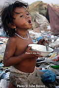 A young worker takes time out from her duties as a bottle and can collector to enjoy a meal at The Stung Meanchey Landfill in Phnom Penh, Cambodia. About 2000 people earn their livings as scavengers at the dump.