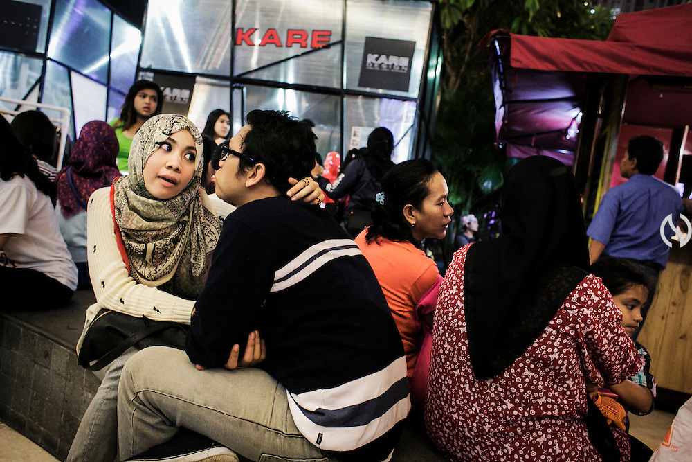JAKARTA - INDONESIA; SATURDAY, SEPTEMBER 13, 2014; INDONESIA ECONOMIC RISING: A couple embraces each other while having week end vacation at Central Park Mall, Jakarta, Indonesia, on Saturday, September 13, 2014. By the increasing income level middle class has abled to enjoy leisure activity during weekend. According to Asian Development Bank's 2014 report, Indonesia economy growth potential is in creative industry after for years relies heavily on natural resources such as mineral mining and palm oil. By the presidency of Joko Widodo, as a product of the third people election after the People Power Revolution in 1998, Indonesia is more confident in the economy growth and optimistic to become equal in quality to Brazil and China's economy growth. The emerging of Indonesia economy for the last one and a half decade after the end of Suharto's Dictatorship has been in significant way, the per capita growth has reached 400% under Susilo Bambang Yudhoyono presidency. Indonesia is home for 74 million of middle class as estimated by Boston Consulting Group, and  will double in 2020.