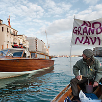"VENICE, ITALY - JANUARY 16:  A protester, sailing next to a Coast Guard power boat on the Grand Canal, holds black listed banner reading ""Stop the large Ships""  on the day of the special meeting discussing the environmental impact of cruises in Venice on January 16, 2012 in Venice, Italy. Protest are mounting in Venice against large cruise ships crossing St Marks's basin after the Costa Concordia tragedy."