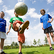 Nederland Nieuw-Lekkerland 14-07-2009 20090714 Foto: David Rozing ..Serie 3 gemeenten Graafstroom, Liesveld en Nieuw-Lekkerland. Jeugd speelt voetbal op voetbalveldje, jongen houdt balletje hoog. Young boys playing soccer outside  playground court  Holland, The Netherlands, dutch, Pays Bas, Europe  Foto: David Rozing