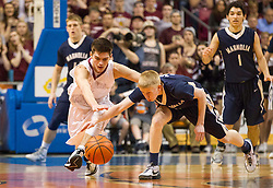 Wheeling Central guard Trenton Smith (11) and Magnolia's Tyler Williamson (3) go for a loose ball during the Class A championship game at the Charleston Civic Center.