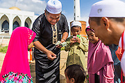 28 JULY 2014 - KHLONG HAE, SONGKHLA, THAILAND: A man hands out cash as a gift to children after Eid services at Songkhla Central Mosque in Songkhla province of Thailand. Eid al-Fitr is also called Feast of Breaking the Fast, the Sugar Feast, Bayram (Bajram), the Sweet Festival and the Lesser Eid, is an important Muslim holiday that marks the end of Ramadan, the Islamic holy month of fasting.   PHOTO BY JACK KURTZ