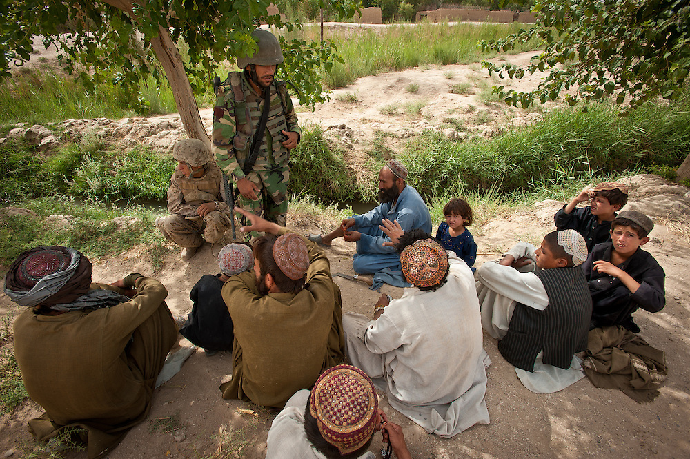 An Afghan National Army officer talks to villagers in Marjah.