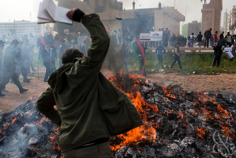 "A Libyan opposition protester throws a copy of the Muammar el-Qaddafi authored Green Book"" onto a burning pile of books and posters during a protest in the eastern city of Benghazi, Libya March 02, 2011. March 02 is traditionally a celebration of the People's Authority Day in Libya, and protesters marked the occasion by burning Qaddafi books, speeches and images. .Slug: Libya.Credit: Scott Nelson for the New York Times"
