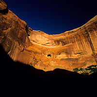 Overhanging red rock cliff glows in evening light, Cayote Gulch, Escalante National Monument, Utah