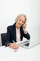 Senior businesswoman writing in book while answering cell phone at desk in office