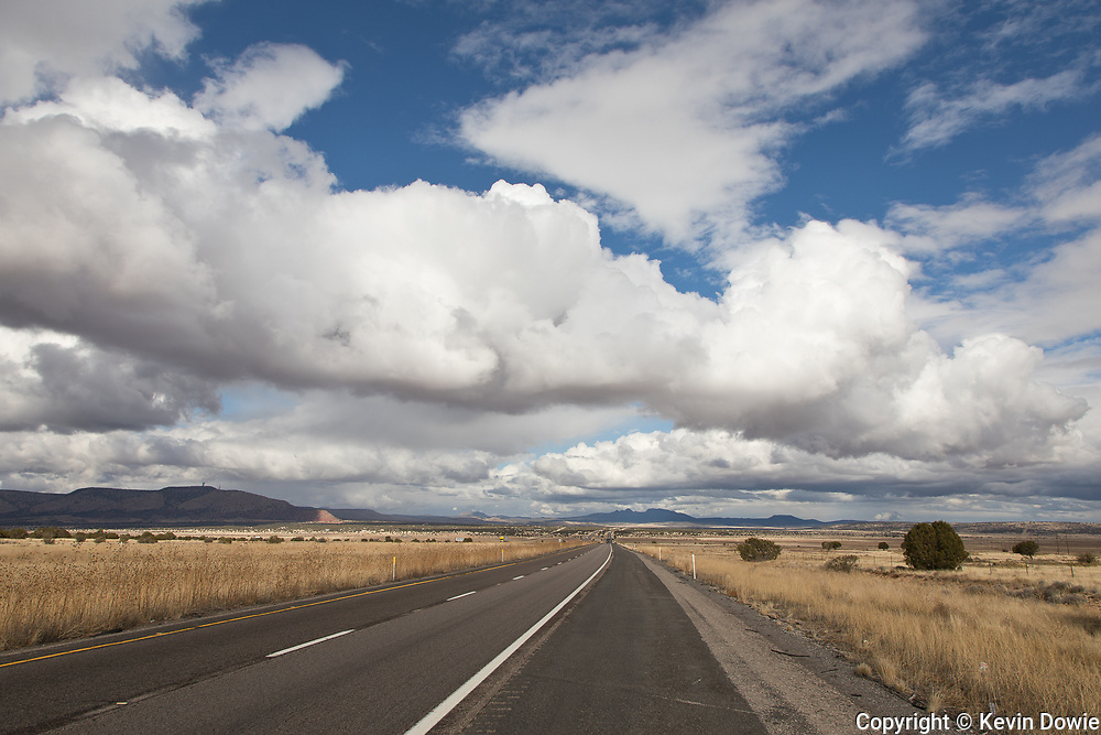 Cumulus clouds and the open road.