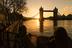 © Licensed to London News Pictures. 26/11/2017. London, UK. Tourists watch sunrise behind Tower Bridge on the River Thames this morning during cold and clear weather. Photo credit: Vickie Flores/LNP