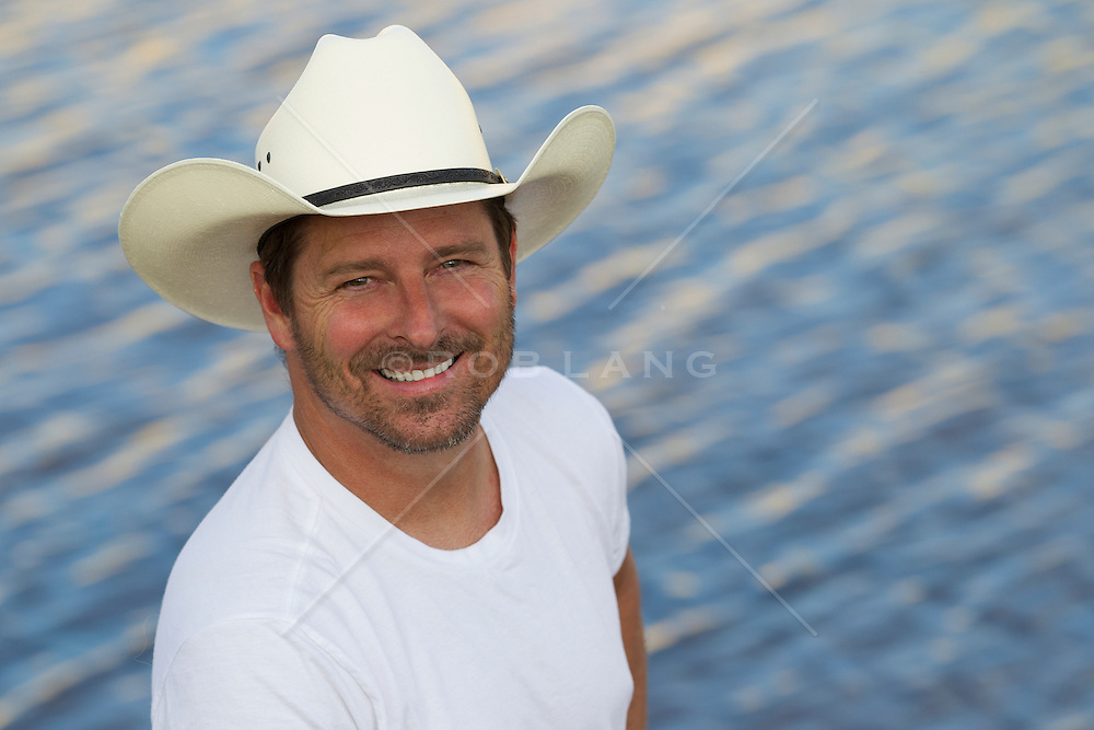 good looking forty something year old cowboy outdoors smiling