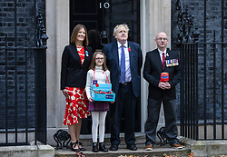 © Licensed to London News Pictures. 28/10/2019. London, UK. Prime Minister Boris Johnson (centre) outside 10 Downing Street as he buys a poppy for the Royal British Legion Poppy Appeal. The EU has agreed to extend the Brexit deadline. Later today MPs will vote on whether to hold a general election in early December. Photo credit: Rob Pinney/LNP