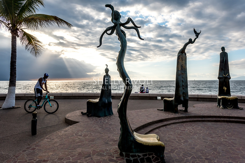 Puerto Vallarta boardwalk or Malecon at dusk with bicycle, people watching sunset by la Rotonda del Mar sculptures (Rotunda of the Sea) by artist Alejandro Colunga.