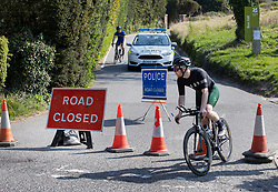 © Licensed to London News Pictures. 10/04/2020. Dorking, UK. Cyclists leave a closed road at Surrey beauty spot Box Hill near Dorking after being turned back by police. Police have closed Box Hill over the Easter Weekend to stop the spread of the coronavirus . The government has warned that people must continue to follow the public health guidance over the Easter weekend. Photo credit: Peter Macdiarmid/LNP
