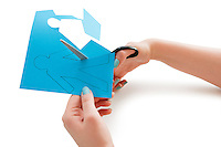 Woman's hand cutting a paper stick figure over white background