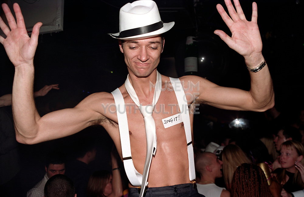 A bare chested man with a label stuck on his chest reading 'Sing it!', Garlands, Liverpool, UK, 2002