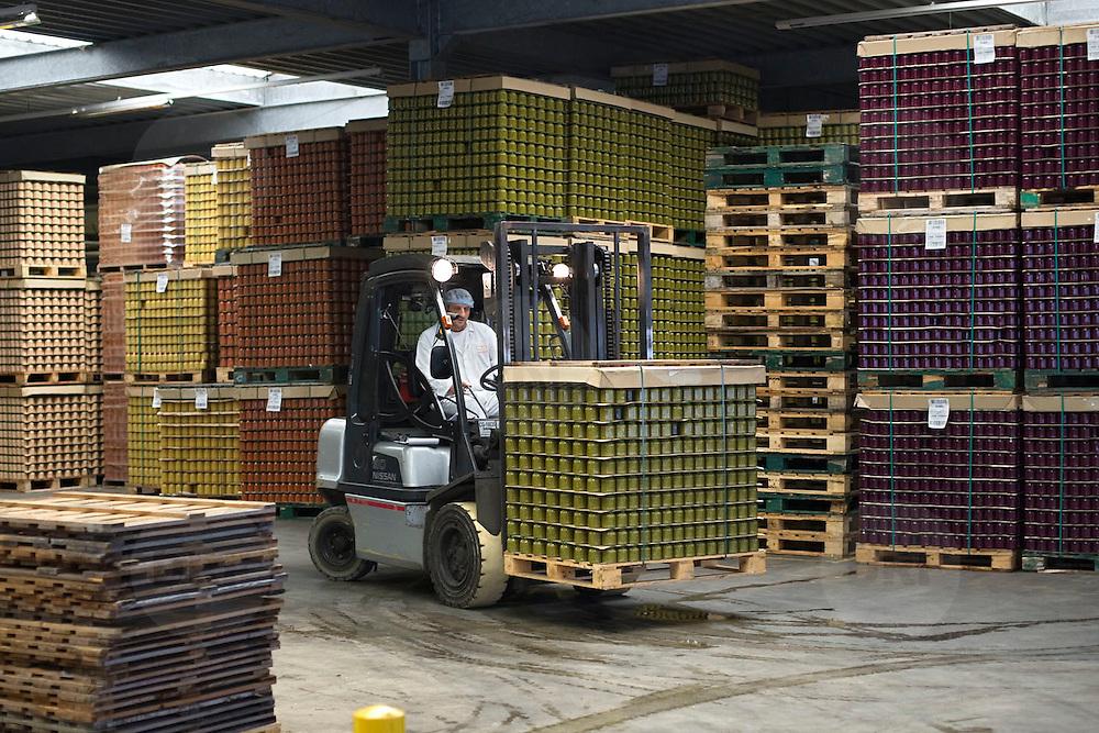 Nederland Giessen 26 augustus 2009 20090826 ..Serie over levensmiddelensector                                                                                      .HAK fabriek, verwerking groente. Magazijn met pallets kleurrijke groente in potten, medewerker transporteert de pallets met een vorkheftruck. Storing vegetables in jars, transporting moving , voedselproductie, voedselproduktie, voedselveiligheid, voorraad, vorkheftruck, werk, werken, werknemer, werknemers, worker, workers..Foto: David Rozing