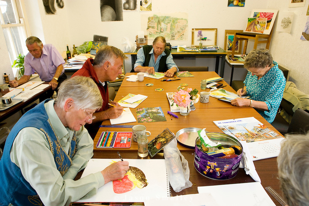 group of elderly people being taught art in a workshop