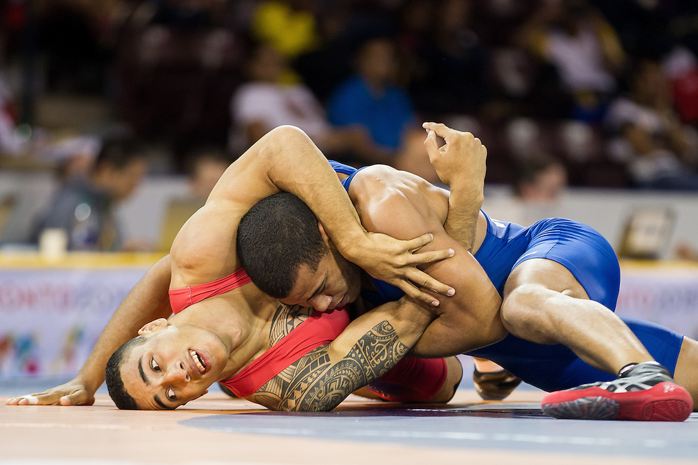 Wuileixis Rivas (R) of  Venezuela tries to roll Alexis Cuero of Colombia during their quarter-final bout in the 85kg class of the men's greco-roman wrestling  at the 2015 Pan American Games in Toronto, Canada, July 15,  2015.  AFP PHOTO/GEOFF ROBINS