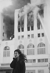 Woman crying outside a building on fire in California