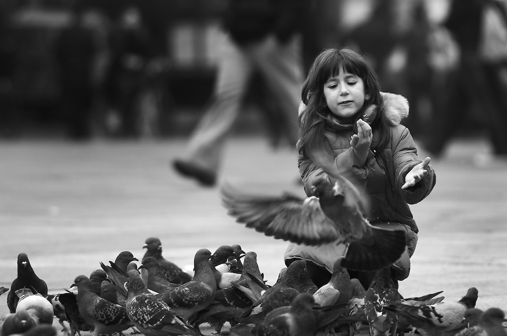 Black and white photography of a girl feeding doves on a square in Bologna Italy.