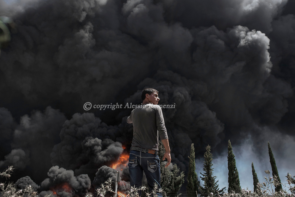 Gaza Strip: A Palestinian boy stands nearby Nusairat power plant as thick black smoke billowed from it on July 29, 2012.<br /> Nusairat power plant is the main source of electricity and the heavy damages reported after the overnight Israeli strikes put in danger of energy shortage the entire Gaza strip.ALESSIO ROMENZI