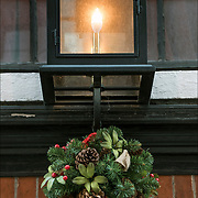 Christmas Wreath with decorations on front door of  James Beard House, 167 West 12th Street in Greenwich Village.<br /> <br /> The tradition of hanging wreath during Christmas is essentially a Christian ritual. This is done during the Christmas season, traditionally used to prepare for the coming of Christ, also known as the Advent season in Christianity. <br /> <br /> Traditionally, the Christmas wreaths were made of evergreen leaves, which are still symbolize the permanence of life.<br /> <br /> A traditional wreath is a circle, which means that there is no beginning or end and that God is eternal.