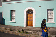A young woman wearing a scarf walks past a colorful house in the Cape Malay quarter of Cape Town, South Africa. For editorial use only.