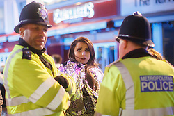 © licensed to London News Pictures. London, UK 01/01/2014. A girl being helped by police officers in Leicester Square, London whilst celebrating the New Year at the first hours of 2014. Photo credit: Tolga Akmen/LNP