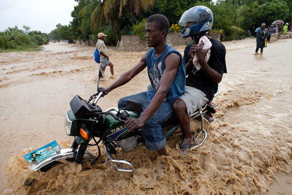 Motorcyclists navigate a road flooded by rain from hurricane Tomas.