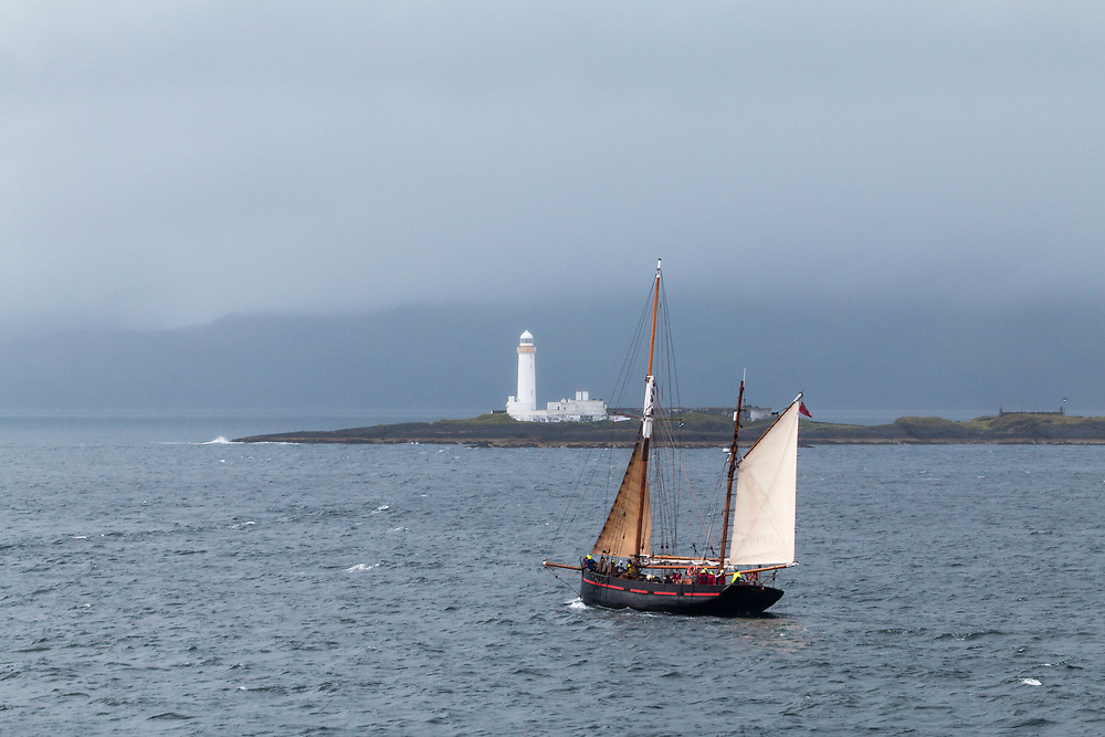 """Leader""; Brixham Sailing Trawler.  Leader looks like a Gaff rigged ketch.  She was built in 1892.  Here she is passing Eilean Musdile Lighthouse in Scotland between the Isl of Mull and the city of Oban."