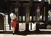 Woman in a red skirt talking in a phone booth on the corner of 57th Street and Broadway in New York City.
