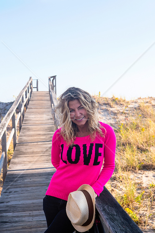 beautiful middle aged woman outdoors on a beach walkway in The Hamptons