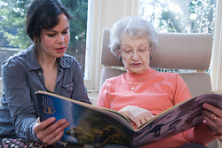 IndependentAge volunteer and older woman reading a magazine together,