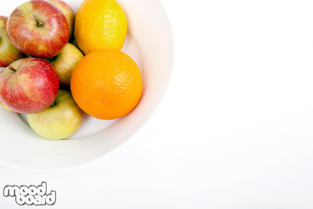 Fresh apples with orange and lemon in plate against white background